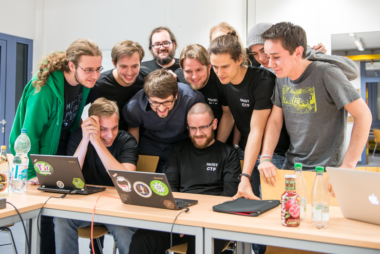 group of hackers staring at a laptop screen